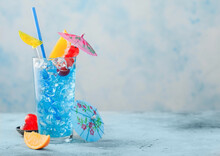 Blue Lagoon Summer Cocktail In Highball Glass With Sweet Cocktail Cherries And Orange Slice With Umbrella On Blue Background.