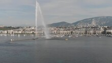 Geneva Switzerland Aeria Shot. Drone Flight Over The City And The Lake. Booths Water, Fountain, City Center, Mountain Boats On The Background.