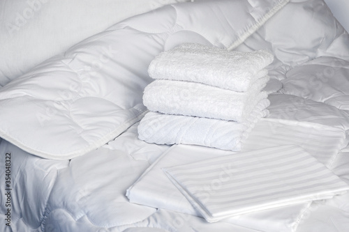 Obraz Towels are on bed. White bedding close-up. Clean terry towels on bedstead. Concept - bed linen at hotel. Sewing industry. Several towels lie on in a pile. Sale of sets with bed linen. Textile - fototapety do salonu