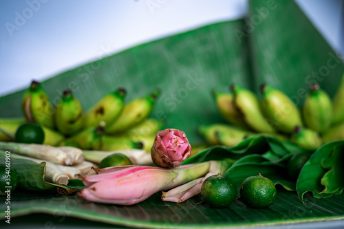 Photo Asian food ingredient with bunga kantan or torch lily, calamansi, lemongrass, tumeric leaves and bananas on a banana leaf background
