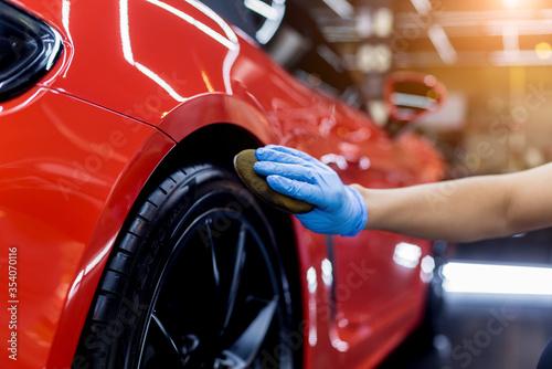 Fototapeta Car service worker polishing car wheels with microfiber cloth. obraz
