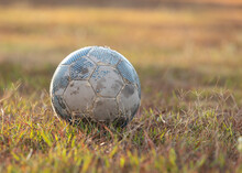 Close Up Old Ball Placed On Green Grass