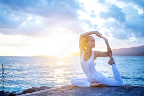 Stampa su Tela Woman practices yoga at seashore