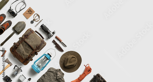 Fotografering Top view of hiking and camping items arranged on abstract white background with