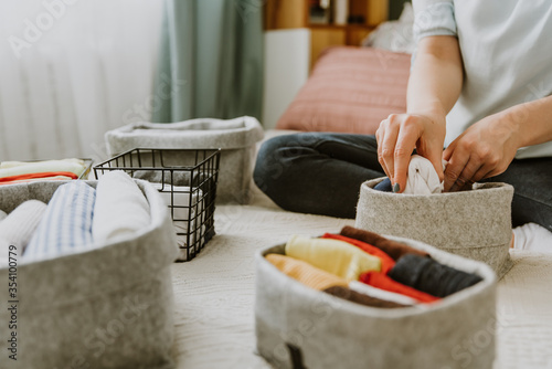 Obraz Woman folding clothes, organizing laundry in boxes and baskets. Concept of minimalist lifestyle and japanese t-shirt folding system. Minimalist wardrobe - fototapety do salonu