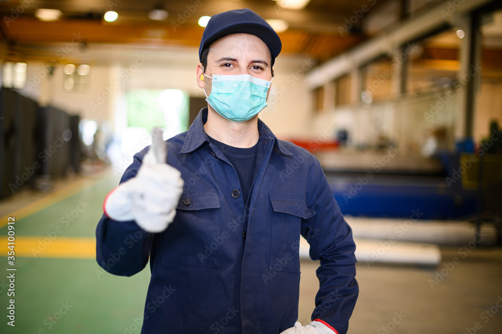 Fototapeta Portrait of a worker in an industrial plant wearing a mask and giving thumbs up, coronavirus concept