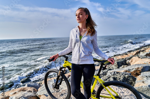 Fototapeta Beautiful young fitness sportswoman with yellow bicycle stands on the stones on the seashore in a clear sunny day. Athletic healthy people with active and sporty lifestyle obraz na płótnie