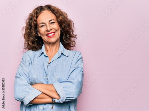 Fotografia, Obraz Middle age beautiful woman wearing casual denim shirt standing over pink background happy face smiling with crossed arms looking at the camera