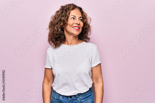 Fototapeta Middle age beautiful woman wearing casual t-shirt standing over isolated pink background looking to side, relax profile pose with natural face and confident smile. obraz