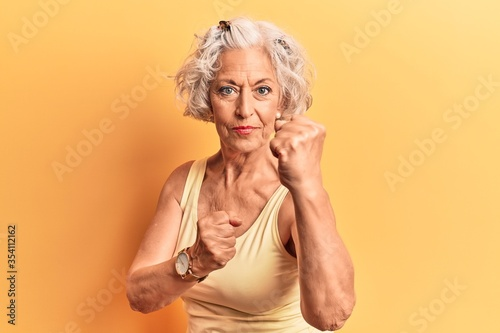 Leinwand Poster Senior grey-haired woman wearing casual clothes ready to fight with fist defense