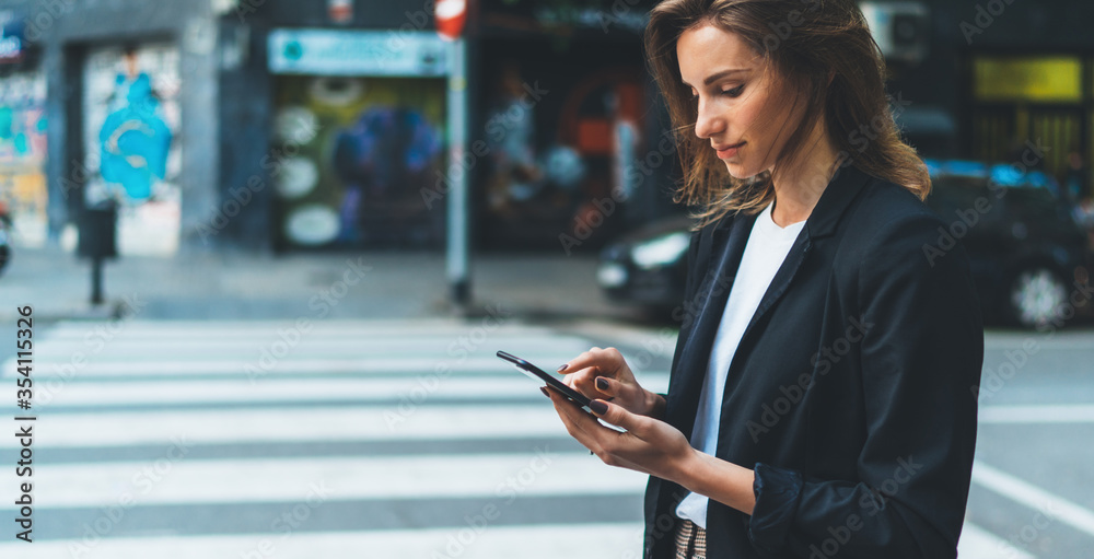 Fototapeta Close-up female hands holding smart phone screen on background of street crosswalk. Young businesswoman using mobile device standing on city road