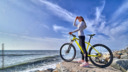 Fototapeta Fitness woman with a bicycle stands on the stones on the seashore and looks into the distance on a clear sunny day. Athletic healthy people with sporty and active lifestyle obraz