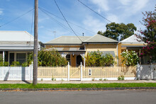 Traditionally Built Row Of Bungalow Cottages In The 20th Century Australian Style With Painted Picket Fences. Some Of The Houses Require Painting.