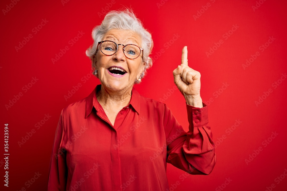 Fototapeta Senior beautiful grey-haired woman wearing casual shirt and glasses over red background pointing finger up with successful idea. Exited and happy. Number one.