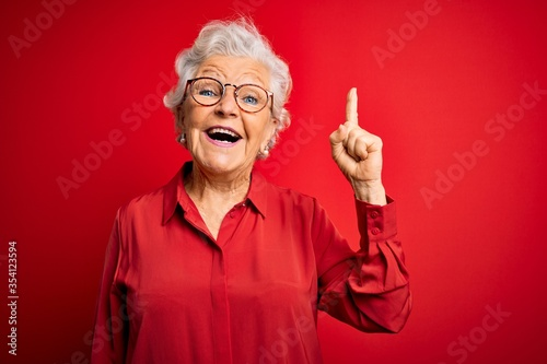 Fotografija Senior beautiful grey-haired woman wearing casual shirt and glasses over red background pointing finger up with successful idea