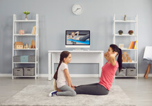 Happy Mother And Daughter Working Out Together To Video Tutorial On TV At Home. Cheerful Family Exercising Indoors Online