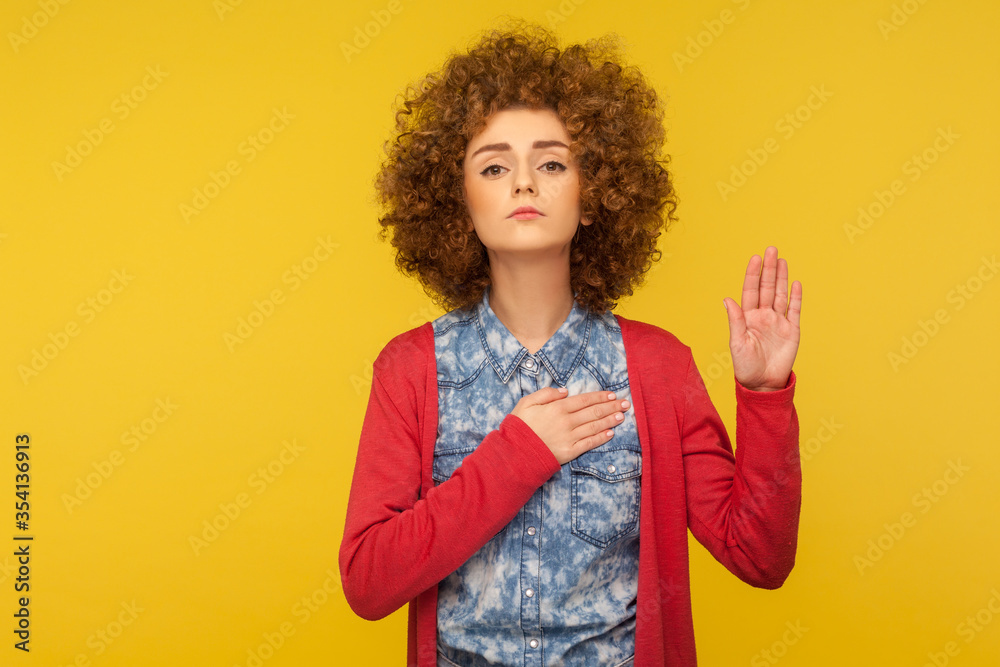 Fototapeta Promise to tell truth! Portrait of woman with curly hair raising hand to take oaths, promise to speak only truth, be sincere and honest, trustworthy evidence. studio shot isolated on yellow background