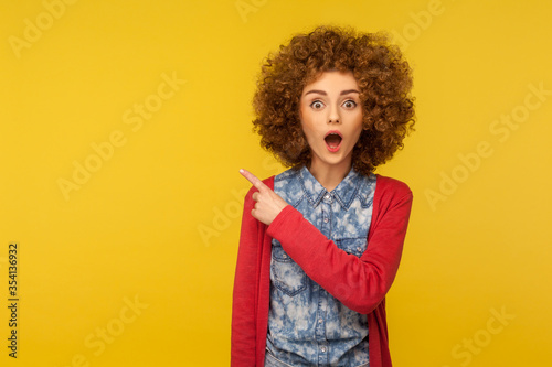 Wow look, advertise here! Portrait of amazed curly-haired pretty woman pointing to the side and looking surprised, showing copy space for commercial presentation Canvas Print