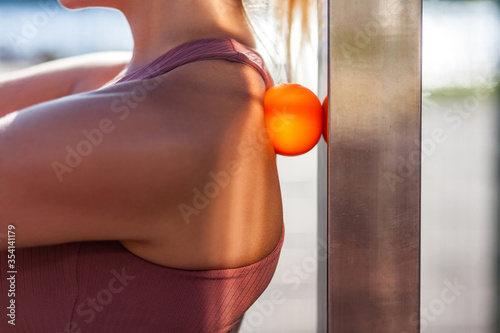 Fotografia Closeup young woman shoulders in tight top leaning on small ball against wall to fix back ache, massaging stiff muscles and sore neck, exercise to relieve spinal pain