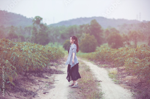 Obraz Carefree happy woman enjoying nature on the street with grass meadow and sunrise. - fototapety do salonu