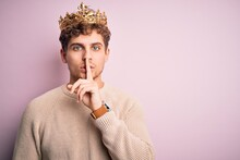 Young Blond Man With Curly Hair Wearing Golden Crown Of King Over Pink Background Asking To Be Quiet With Finger On Lips. Silence And Secret Concept.