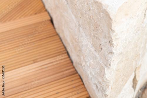 Fototapeta Bangkirai wooden deck and natural stone wall on a terrace obraz na płótnie