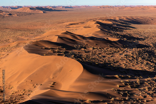 Aerial view of the sand dunes, located in the Namib Desert, in the Namib-Naukluft National Park, Namibia at sunrise.