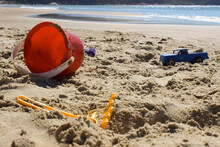 Someone Has Forgotten Their Toys On The Beach, A Bucket, A Plastic Sand Rake And A Police Van Show It.