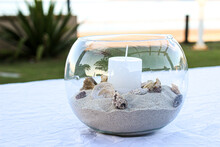 Detail Of A Centerpiece With A Maritime Theme, In Addition To The Candle In The Center And The Sand Around It We Have Several Snail Shells On Top Of A Table On The Garden Next To The Shore