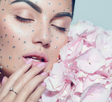 Beauty fashion Woman face decorated with gem stones, crystals. Closeup Portrait with Hydrangea. Model girl with holiday Glamour shiny professional make up with gems, jewellery, jewelry, accessories