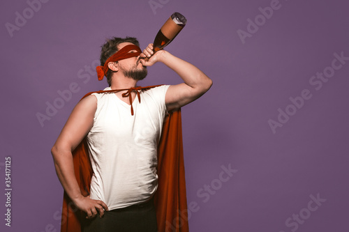 Fotografie, Tablou Super antihero man drinks alcohol from the throat of a bottle