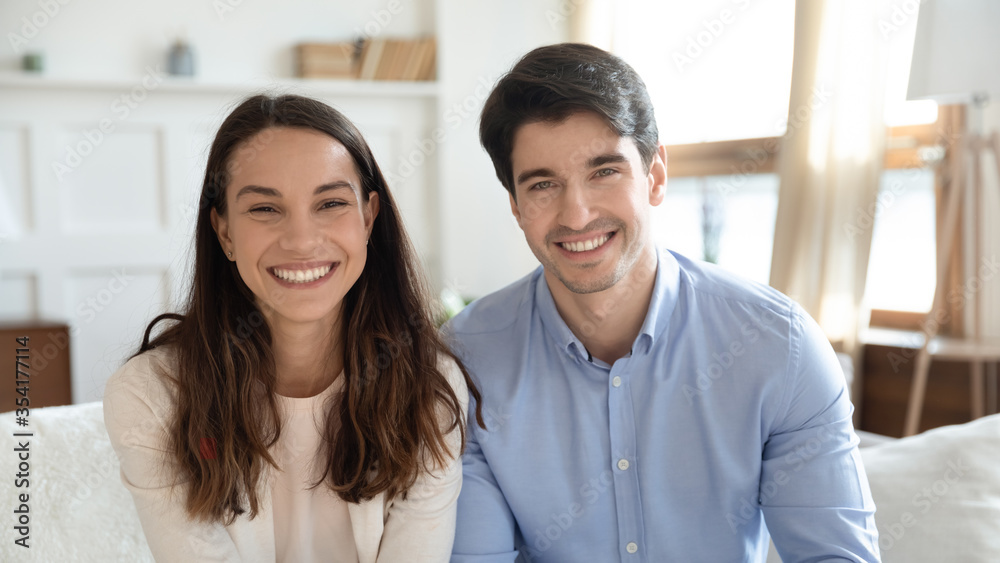 Fototapeta Headshot portrait of smiling young caucasian man and woman sit on sofa in living room having web video call, happy millennial couple have fun talk speak on webcam internet conference at home together
