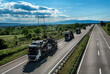 Fleet of car carrier trailers, known variously as a car-carrying trailers, car haulers, autotransport trailers, on a beautiful road, in a sunny summer day. A beautiful blue sky with clouds.