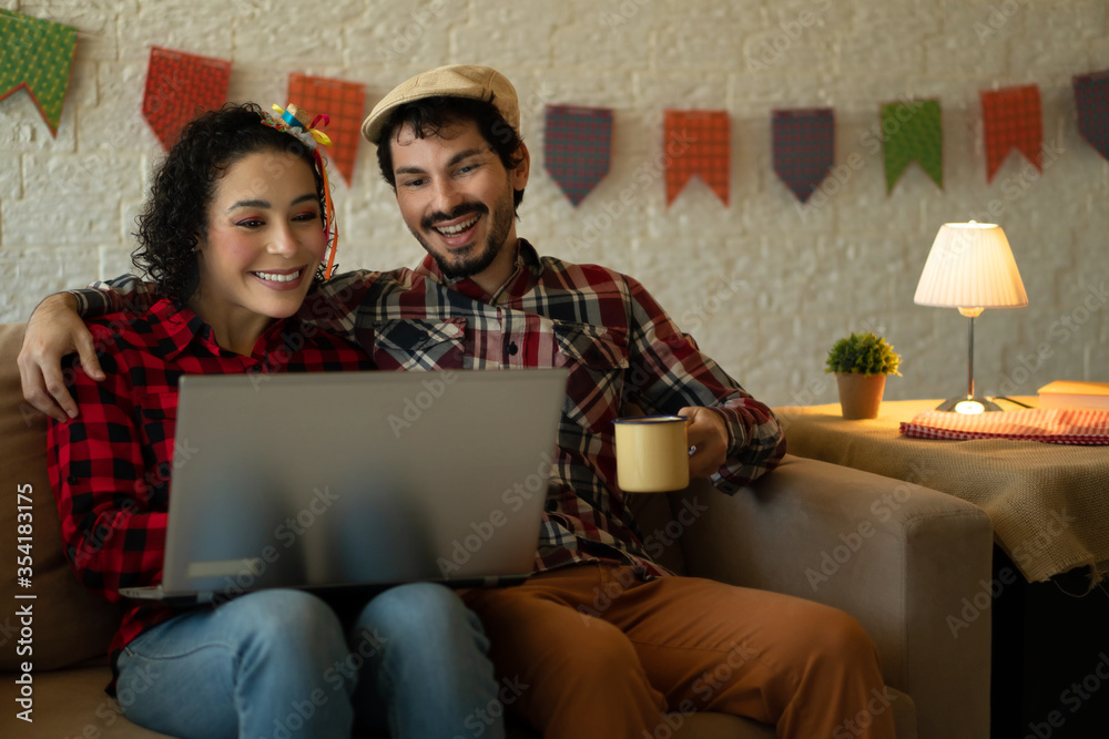 Fototapeta Happy cheerful Young adult brazilian couple relaxing and watching video during quarantine Inside the house in living room. Traditional brazilian june festival, party, celebration concept.