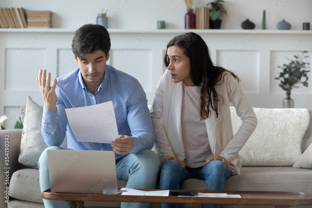 Fototapeta Distressed young caucasian family have fight about household finances expenditures, worried millennial couple pay bills online, anxious about bankruptcy or financial problems, receive bank debt notice