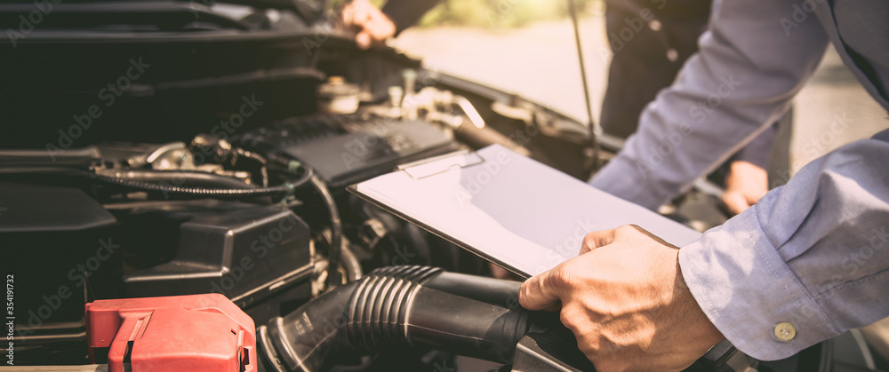Fototapeta Auto mechanic using checklist for car engine systems after fixed. concepts of car insurance support and services.