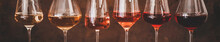 Various Shades Of Rose Wine In Stemmed Glasses Placed In Line From Light To Dark Colour On Concrete Table, Rusty Brown Background Behind, Wide Composition. Wine Bar, Wine Shop, Wine Tasting Concept
