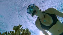 UNDERWATER: Young Caucasian Woman In Black Bikini Snorkels Past A Bleached Coral