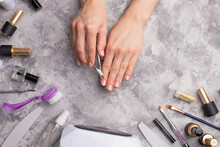 The Girl Does Nails On A Concrete Gray Background, With Tools For Nail Care. Top View. Beauty And Hygiene To Please The Nails.