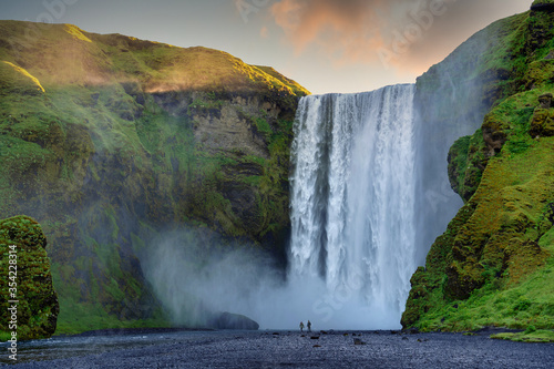 Fototapety, obrazy: Two male and female tourists are walking at Skogafoss Falls in southern Iceland. In the morning, the sun rose from behind the mountains with green grass. This is a popular tourist destination.