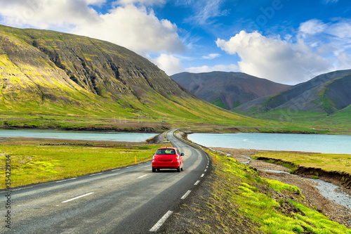 A red car runs on the highway in the Icelandic countryside. Amidst the great nature of mountains and lakes, in the summer there is grass all over In the concept road trip Holiday driving