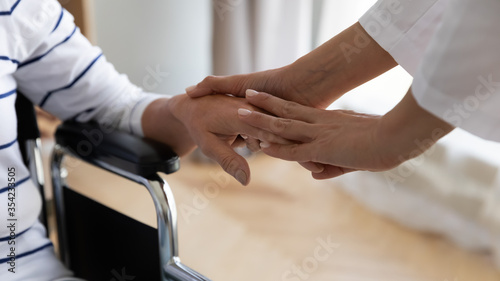 Fotografía Disabled elderly woman sitting in invalid carriage her palm holding stroking caring nurse close up image