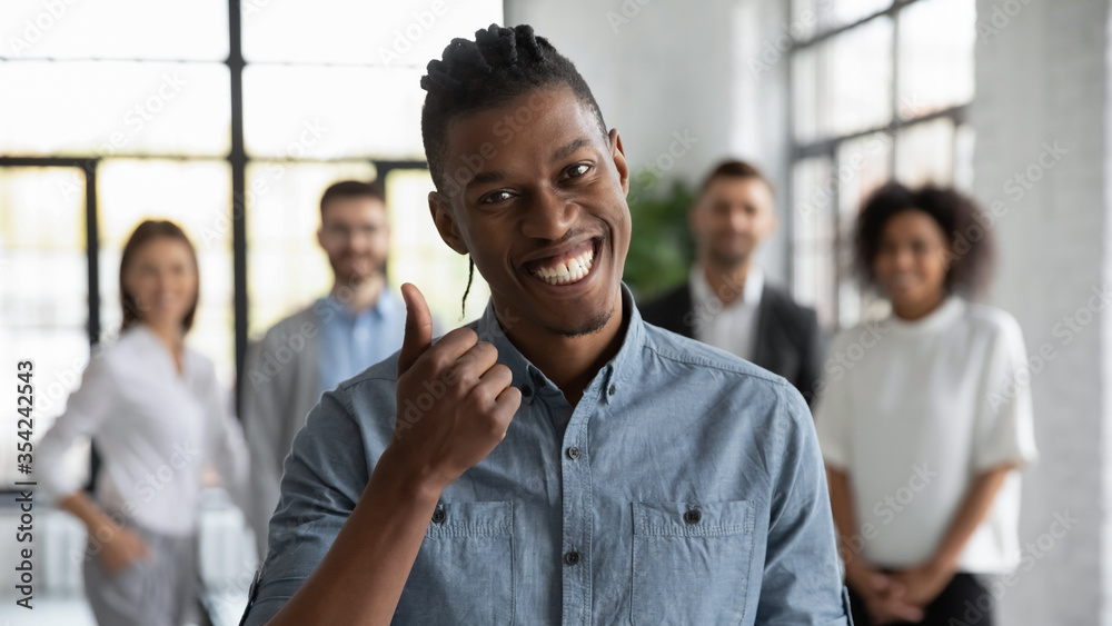 Fototapeta Head shot portrait smiling African American employee showing thumb up, standing with colleagues in modern office room, looking at camera, recommending corporate service, good career, human resources