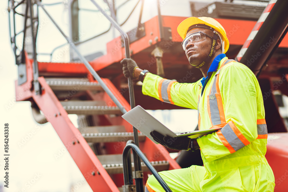 Fototapeta Black African Staff foreman intend to work loading worker using laptop computer to control cargo shipping in logistic warehouse.