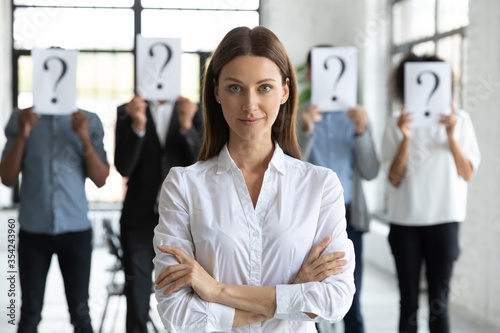 Head shot portrait confident businesswoman hr manager with candidates standing behind, workers hiding faces behind papers with question marks, identity and equality at work, recruitment process