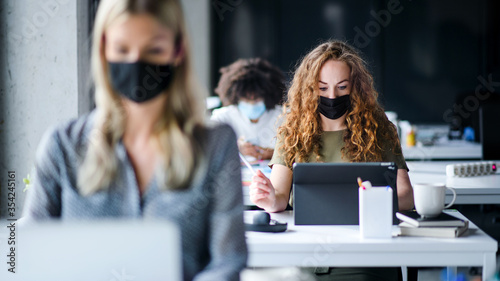 Young people with face masks back at work or school in office after lockdown. - 354245161