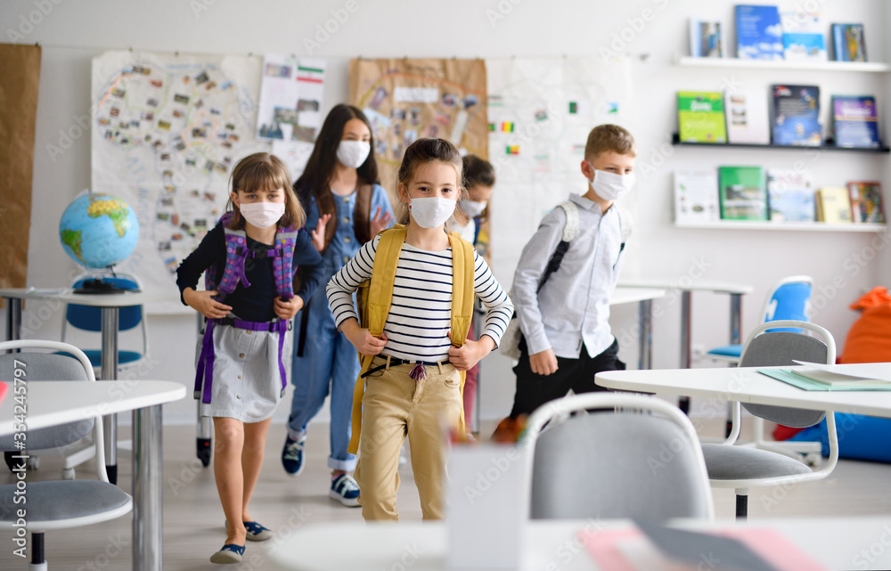 Fototapeta Group of children with face mask back at school after covid-19 quarantine and lockdown.