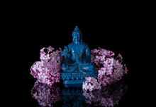 Blue Medicine Buddha Framed By Pink Lilac Flowers On A Black Background With Reflection