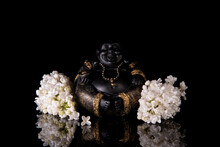 Chinese Laughing Buddha Hotei Or Budai Framed By White Lilac Flowers On A Black Background With Reflection