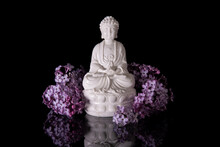 White Buddha Framed By Pink Lilac Flowers On A Black Background With Reflection